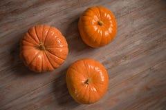 Tres pumkins anaranjados en los tableros de madera fotografía de archivo