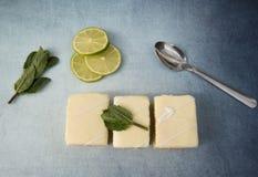 Tres rebanadas de la torta del limón con las cales y las hojas de menta Fotos de archivo