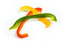Tres rebanadas de paprikas rojos, amarillos y verdes Foto de archivo libre de regalías