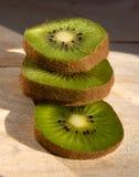 Tres rebanadas frescas del kiwi apiladas en un tablero de madera Fotos de archivo libres de regalías