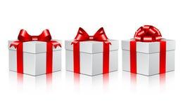 Tres rectángulos de regalo blancos con arqueamientos rojos. Foto de archivo