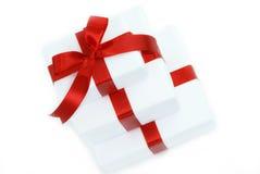 Tres rectángulos de regalo blancos con la cinta roja Imagenes de archivo