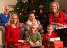 Tres regalos de la Navidad de la apertura de la familia de la generación en imagen de archivo libre de regalías