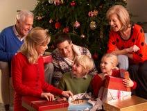 Tres regalos de la Navidad de la apertura de la familia de la generación Imágenes de archivo libres de regalías