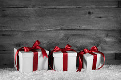 Tres regalos de Navidad blancos rojos en viejo fondo gris de madera fotos de archivo libres de regalías