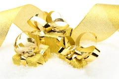 Tres regalos de oro de la Navidad con la cinta en nieve Fotos de archivo
