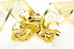 Tres regalos de oro de la Navidad con la cinta en nieve Fotografía de archivo