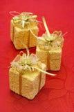 Tres regalos en fondo rojo Imagenes de archivo