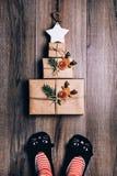 Tres regalos envueltos en papel marrones presentados en la forma de un árbol de navidad con la estrella en el top Pies de la muje Foto de archivo