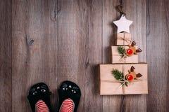 Tres regalos envueltos en papel marrones presentados en la forma de un árbol de navidad con la estrella en el top Pies de la muje Imagenes de archivo