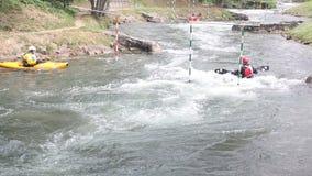 Tres remeros nadan en un kajak contra el río metrajes