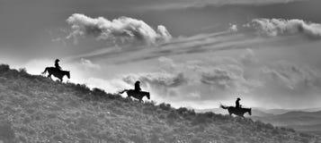 Tres Ridge Riders Silhouette y la tierra en estilo del pano y blanco y negro imágenes de archivo libres de regalías