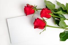 Tres rosas con la tarjeta en blanco Foto de archivo