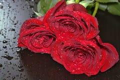 Tres rosas rojas en la tabla de madera negra Imagen de archivo libre de regalías