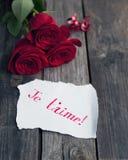 Tres rosas rojas en la tabla rústica con el t'aime manuscrito del je de las palabras Imagenes de archivo