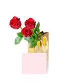 Tres rosas rojas en una tarjeta de oro del bolso y de nota del regalo Imagen de archivo libre de regalías