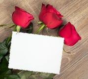Tres rosas rojas y hoja en blanco en la madera Foto de archivo