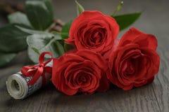 Tres rosas rojas y manojos de dólares Fotografía de archivo