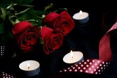Tres rosas rojas y velas ardientes Imagenes de archivo