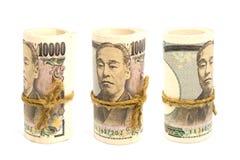 Tres ruedan para arriba del dinero Yen Banknote On White Background imagen de archivo