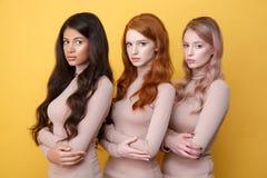 Tres señoras con los brazos cruzados que presentan en estudio Foto de archivo libre de regalías