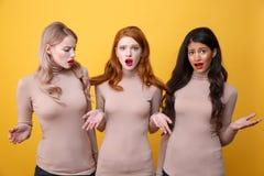 Tres señoras confusas que se colocan con el pelo atado Foto de archivo