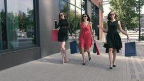 Tres señoras jovenes atractivas están caminando con sus compras almacen de video