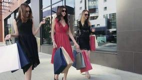 Tres señoras jovenes atractivas que caminan abajo de la calle con metrajes