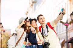 Tres selfies felices de la toma de los amigos con el teléfono móvil Imagen de archivo libre de regalías