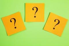 Tres signos de interrogación anaranjados en fondo verde Imagen de archivo