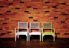 Tres sillas con el fondo rojo hermoso de la pared de ladrillo Imagen de archivo libre de regalías