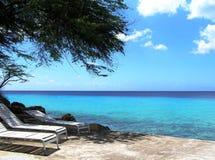 Tres sillas de cubierta blancas en la sombra de un árbol en una playa tropical fotos de archivo