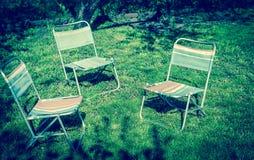 Tres sillas en el césped Imagenes de archivo