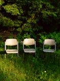Tres sillas en jardín Imagenes de archivo