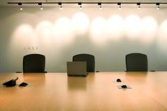 Tres sillas y computadoras portátiles en sala de reunión corporativa. Foto de archivo