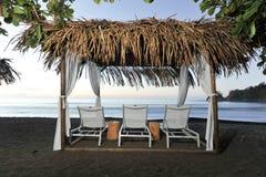 Tres sillones en una playa cubierta Imagen de archivo