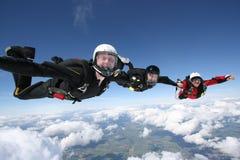 Tres skydivers forman una línea fotos de archivo libres de regalías