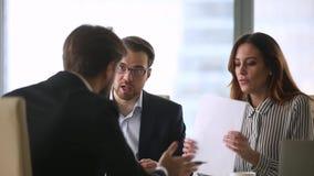 Tres socios comerciales que se sientan en el escritorio que disputa sobre términos de contrato metrajes