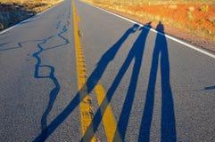 Tres sombras en el camino fotografía de archivo
