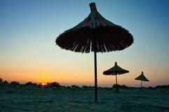 Tres sombrillas y la puesta del sol en la playa Imagen de archivo