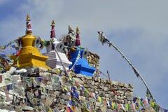 Tres stupas budistas: el amarillo, el blanco y el azul en la cima de la albañilería, colgaron con las banderas tibetanas coloread Fotos de archivo