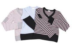 Tres suéteres coloridos de moda en un blanco Fotografía de archivo libre de regalías