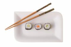 Tres sushirolls y palillos del makizushi Fotos de archivo libres de regalías