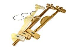 Tres suspensiones de capa plásticas de Brown con los ganchos del metal Imágenes de archivo libres de regalías