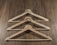 Tres suspensiones de madera en un fondo de madera más oscuro foto de archivo