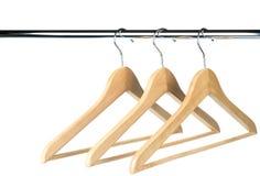 Tres suspensiones de madera vacías de /clothes de la capa en un carril de la ropa Fotografía de archivo libre de regalías