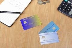 Tres tarjetas de crédito en un escritorio con la libreta y la calculadora Foto de archivo libre de regalías