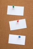 Tres tarjetas en blanco fijadas a un tablero del corcho Imagenes de archivo