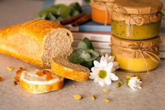 Tres tarros cerrados con la fruta atascan y cuted el pan con las pasas están en la tabla Imagen de archivo