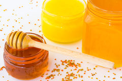 Tres tarros con la miel floral en un fondo blanco Miel del cazo Fotografía de archivo